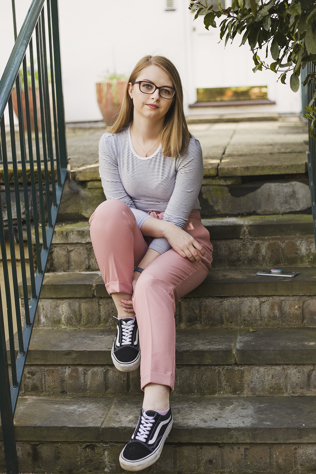 Girl sitting on steps wearing pink trousers and a predominently white striped top.
