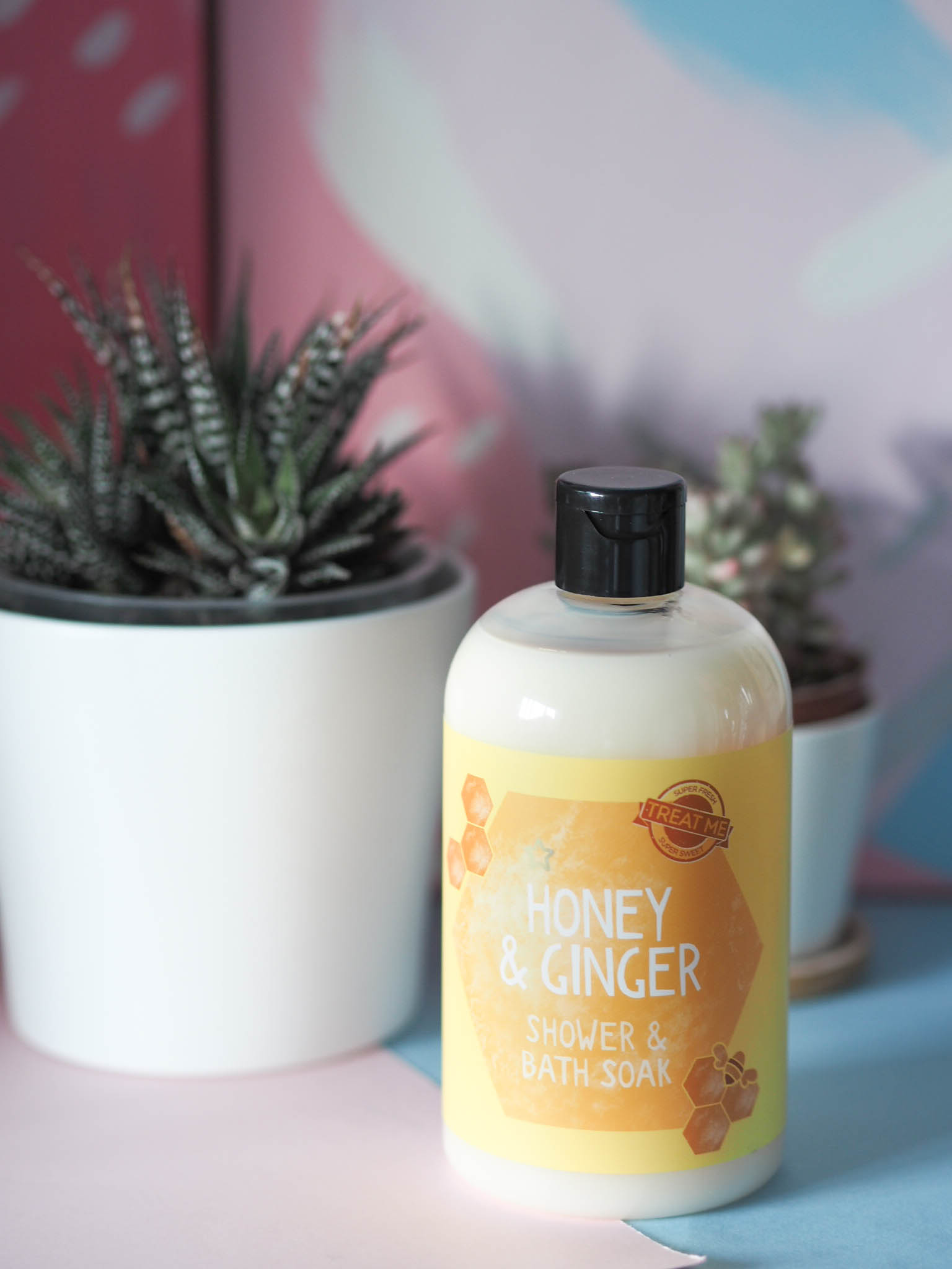 Superdrug honey and ginger body wash in front of potted plants
