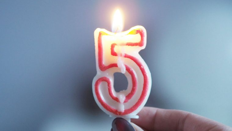 A burning candle in the shape of the number 5 is held against a blue background
