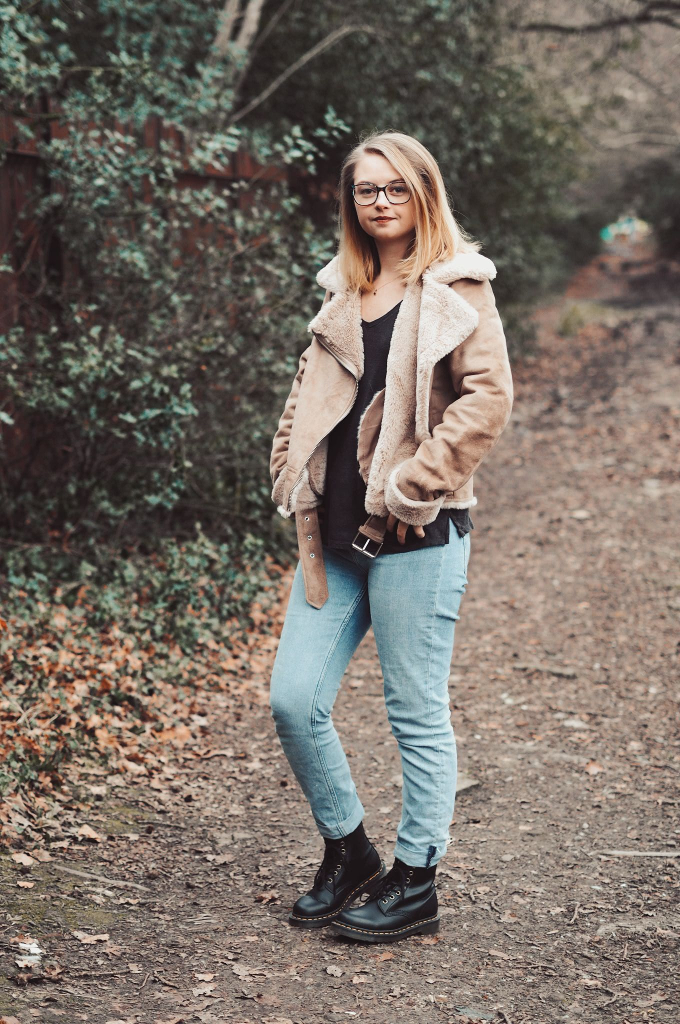 Blonde girl in light brown suede jacket in the woods, with lightwash blue jeans