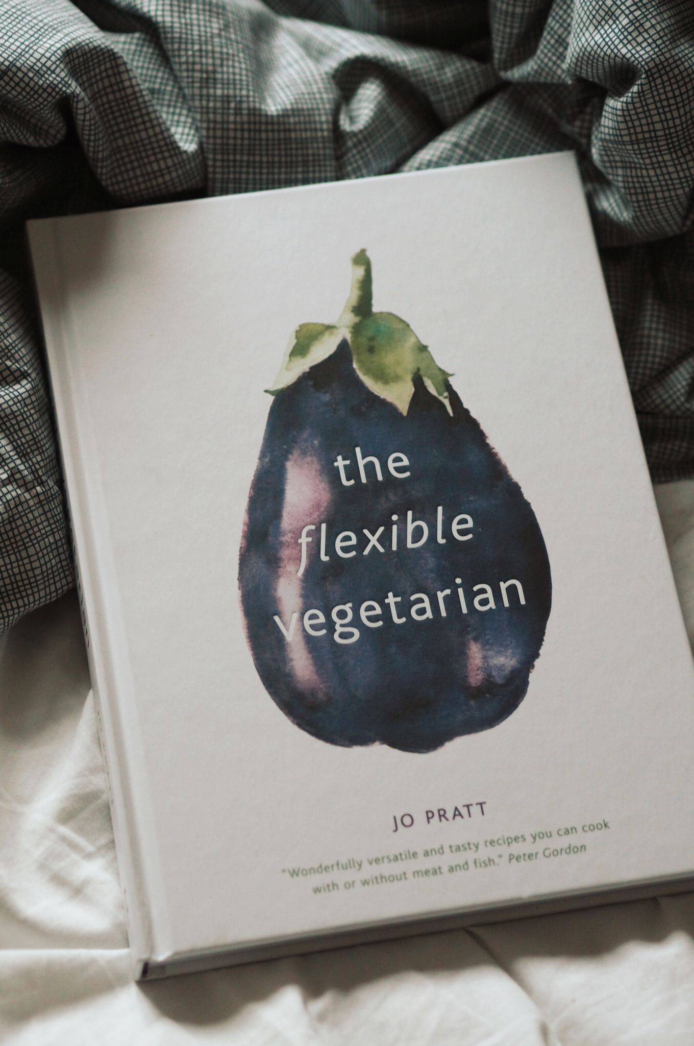 A white-covered book entitled 'The Flexible Vegetarian' sits on white bed sheets. The book has a large image of an aubergine or eggplant on the cover and is written by Jo Pratt.