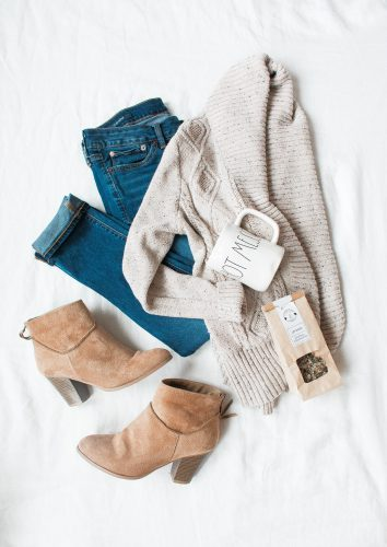 Clothes laying on a bed; including dark blue jeans, cream cardigan, beige heeled boots and a mug