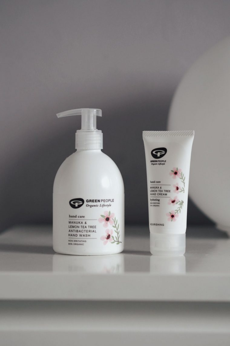 white hand soap and hand cream bottles on white surface in front of purple background