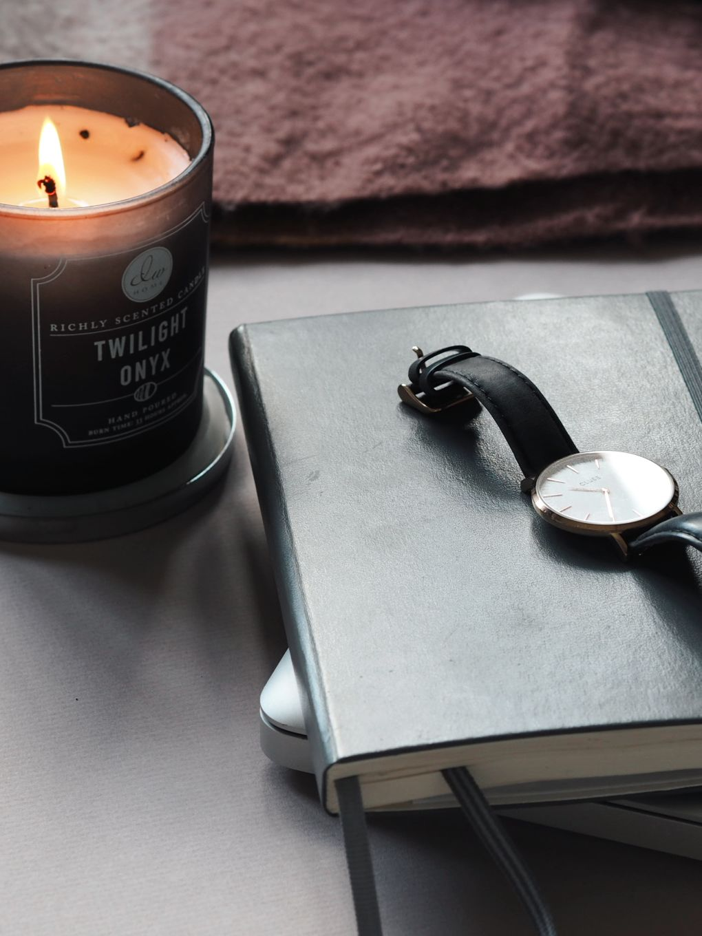 Lit candle sitting to the left of a grey notebook with a black strapped watch on top of an orange and pink hued backdrop