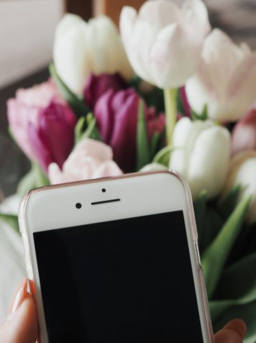 Rose gold iphone in front of white and pink tulips