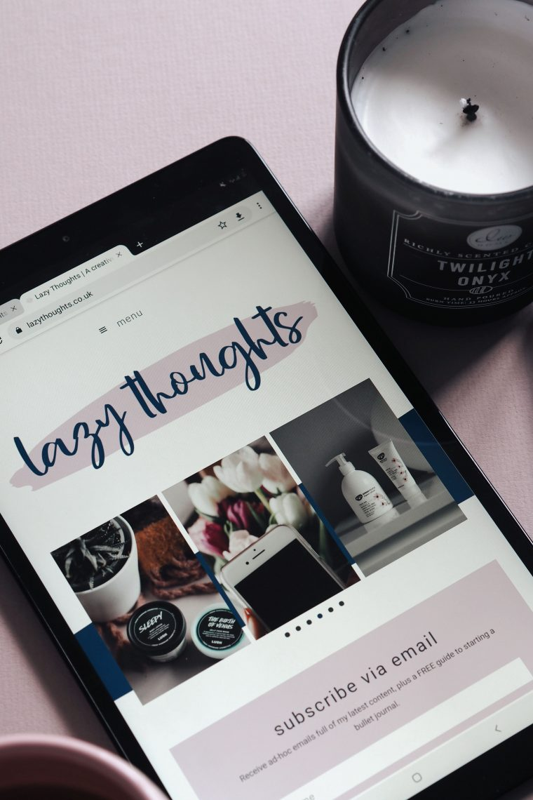 Lazy Thoughts blog on a tablet screen with candle