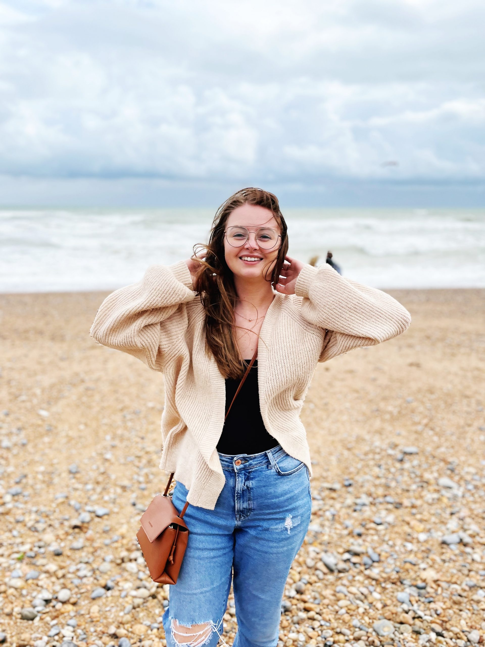 Brunette woman stood on beach with hands in hair